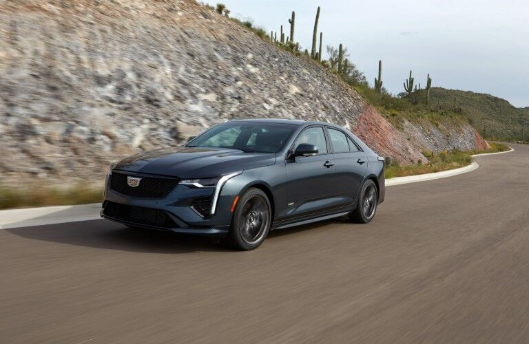 2020 Cadillac CT4-V exterior shot with gray metallic paint color driving down a country highway near grassy cliffs