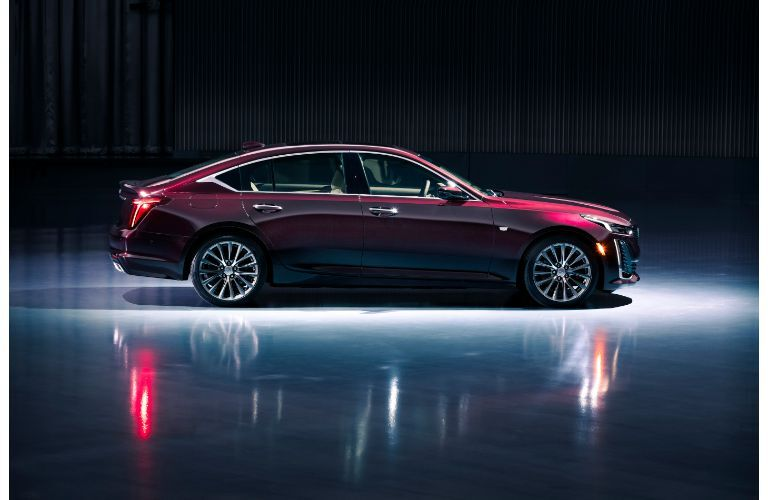 2020 Cadillac CT5 Premium Luxury exterior side shot with dark red maroon paint color lit in an empty showroom