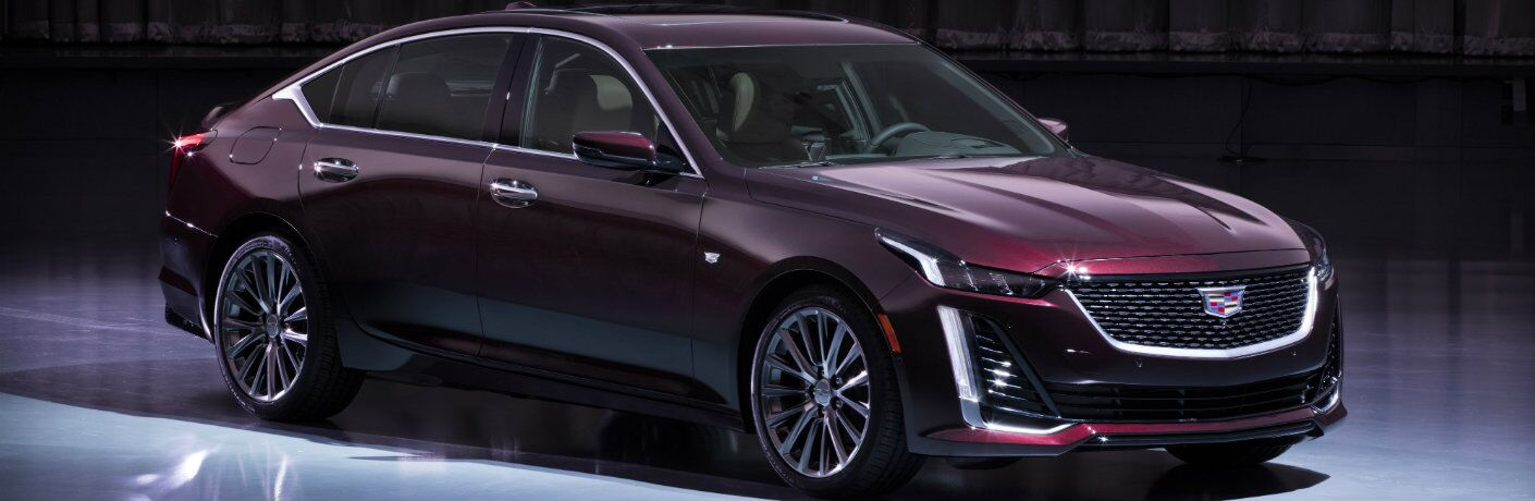 2020 Cadillac CT5 Premium Luxury with dark red maroon paint color presented on a lit up showroom stage