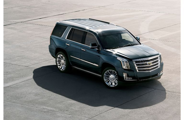 2020 Cadillac Escalade exterior overhead shot with deep blue paint color framed by a sun and shadow