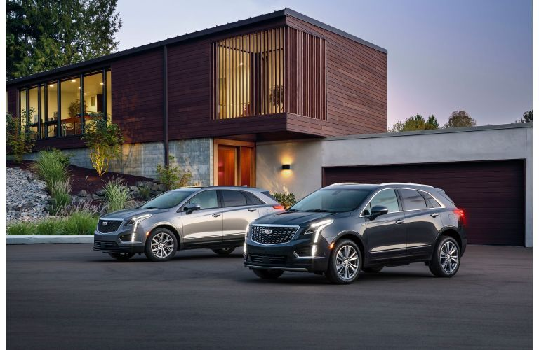 2020 Cadillac XT5 Premium Luxury and Sport models parked outside a luxury home garage on the driveway