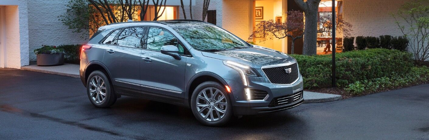 2020 Cadillac XT5 Sport SUV exterior shot with gray paint color and LED headlights on parked on a road right outside a fancy home with a green terrace of bushes and trees