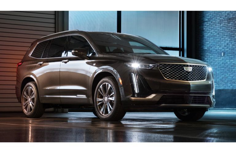 2020 Cadillac XT6 SUV exterior shot at night on a wet road as LED headlights shine