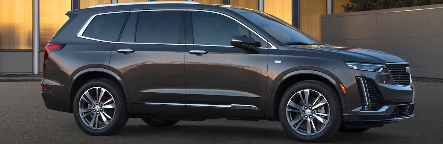 2020 Cadillac XT6 SUV exterior side shot with brown metallic paint color parked outside an apartment building