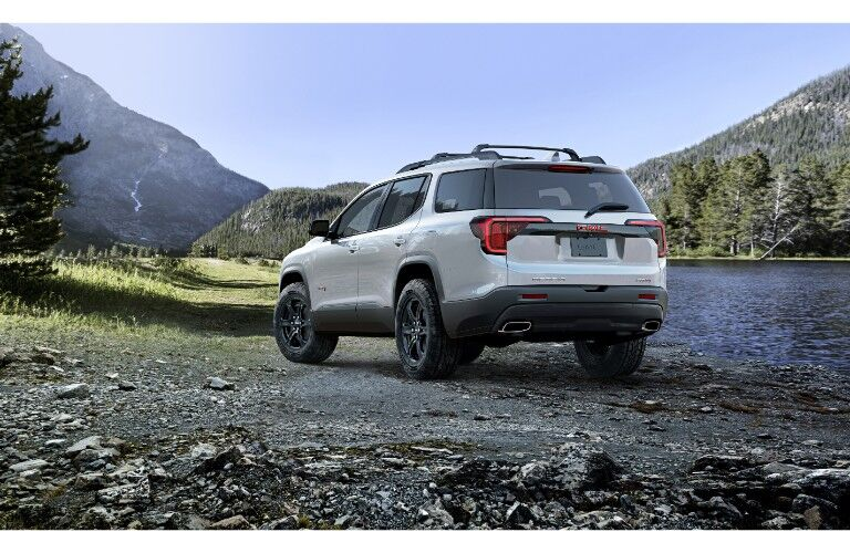 2020 GMC Acadia AT4 exterior rear shot with white metallic paint color parked on a rocky beach near a river and mountains of forests