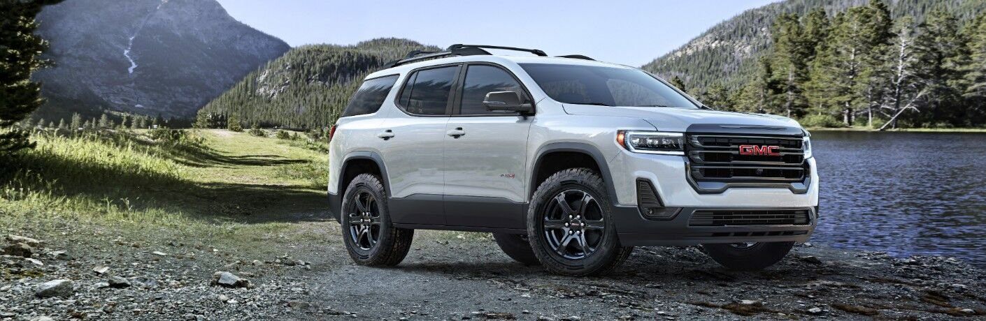 2020 GMC Acadia AT4 exterior shot with white metallic paint color parked on a rocky beach near a river and mountains of forests
