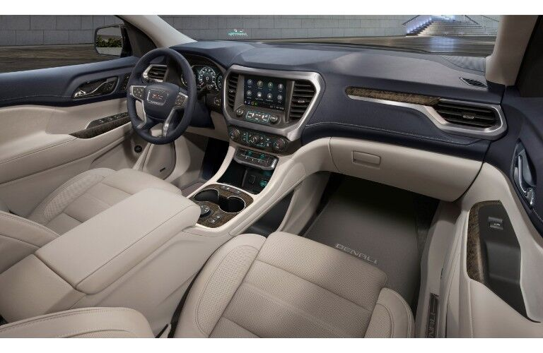 2020 GMC Acadia Denali interior shot of front seating, floor mats, steering wheel, and dashboard layout