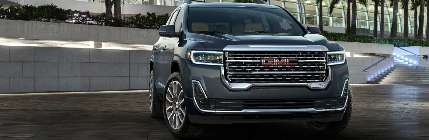 2020 GMC Acadia exterior front shot with dark gray paint color parked outside a fancy glass dome building on the plaza