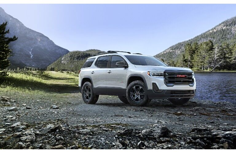 2020 GMC Acaida AT4 exterior shot with white metallic paint color parked on a rocky beach near a river and mountains of forests