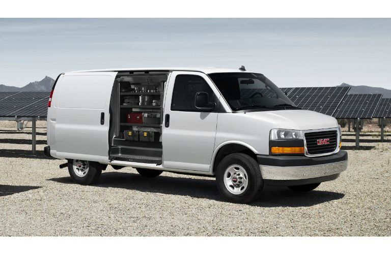 2020 GMC Savana Cargo van exterior side shot with white paint color and door open and stocked up with storage and cargo