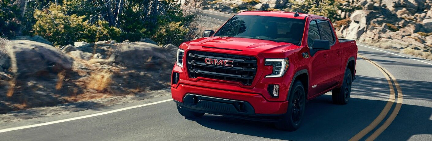 2020 GMC Sierra 1500 exterior shot with red paint color driving on a curving road through a rocky, uphill forest