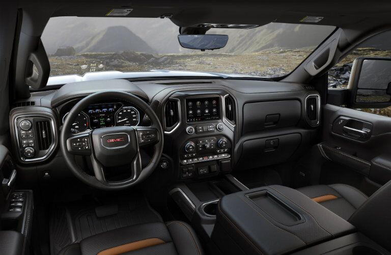 2020 GMC Sierra 2500HD AT4 interior shot of front seating, steering wheel, and dashboard layout
