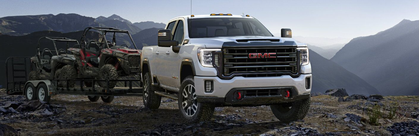 2020 GMC Sierra 2500HD AT4 model exterior shot with white paint color parked on a rocky cliff with a trailer of all-terrain buggy tractors