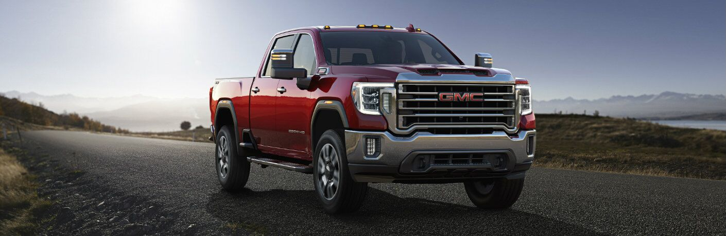 2020 GMC Sierra 2500HD exterior shot with red paint color parked in the country on a fresh black asphalt road
