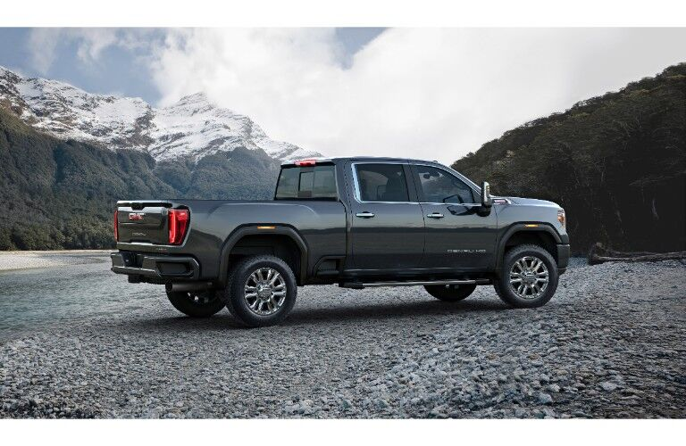 2020 GMC Sierra 2500 HD Denali exterior side shot of profile with snow capped mountains in the background above a forest_o