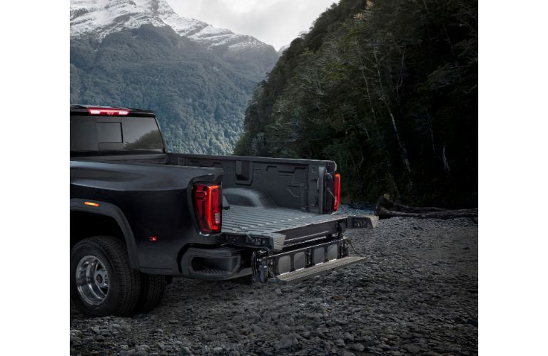2020 GMC Sierra 3500HD exterior shot of truck bed unfolded while parked on a stone gravel field