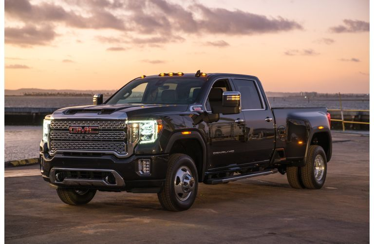 2020 GMC Sierra 3500HD exterior shot parked next to the sea with LED headlights on as the sun sets