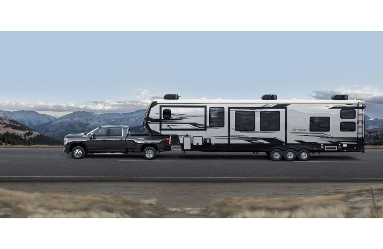 2020 GMC Sierra 3500HD exterior side shot pulling a huge RV trailer down a highway