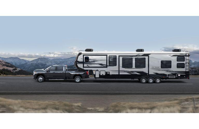 2020 GMC Sierra 3500HD exterior side shot pulling a huge RV trailer down a highway