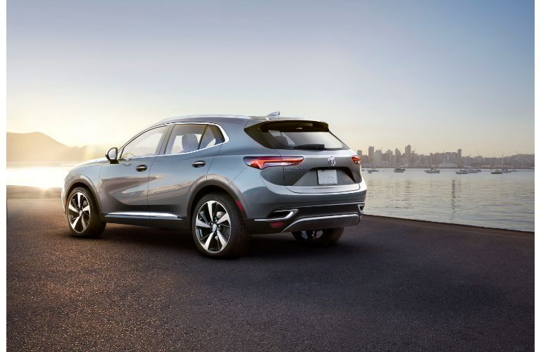 2021 Buick Envision exterior rear shot with metallic paint color parked on a beach near boating docks and a bright sun