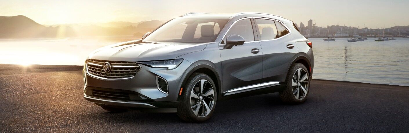 2021 Buick Envision exterior shot with metallic paint color parked on a beach near boating docks and a bright sun