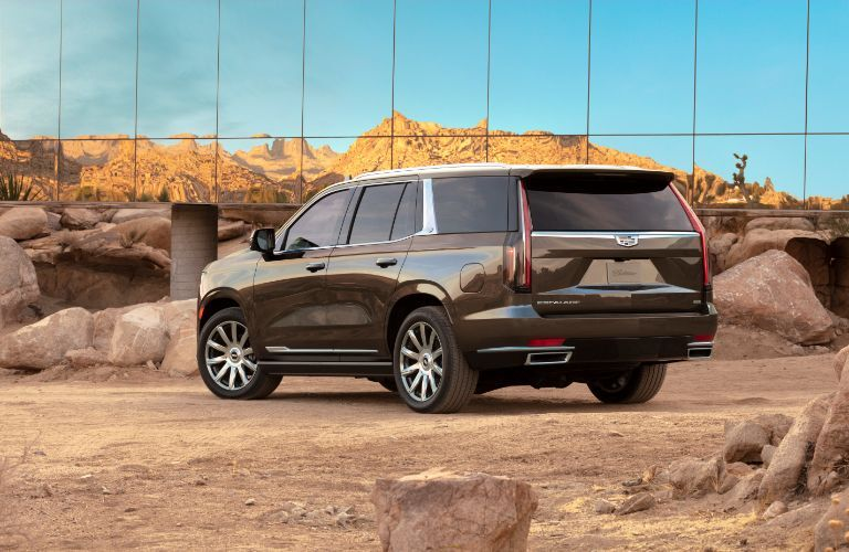 2021 Cadillac Escalade exterior rear shot with brown metallic paint color parked on a dirt plain near a glass reflective building