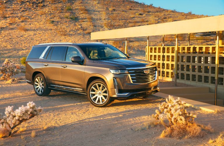 2021 Cadillac Escalade exterior shot with brown metallic paint color parked near a building in a dry desert area