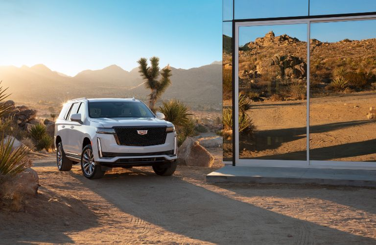 2021 Cadillac Escalade exterior shot with white paint color and new mesh grille parked on a desert plain near a glass building as the sun sets