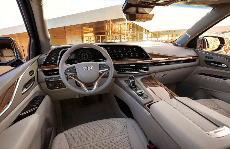 2021 Cadillac Escalade interior shot of front seating, steering wheel, and dashboard design