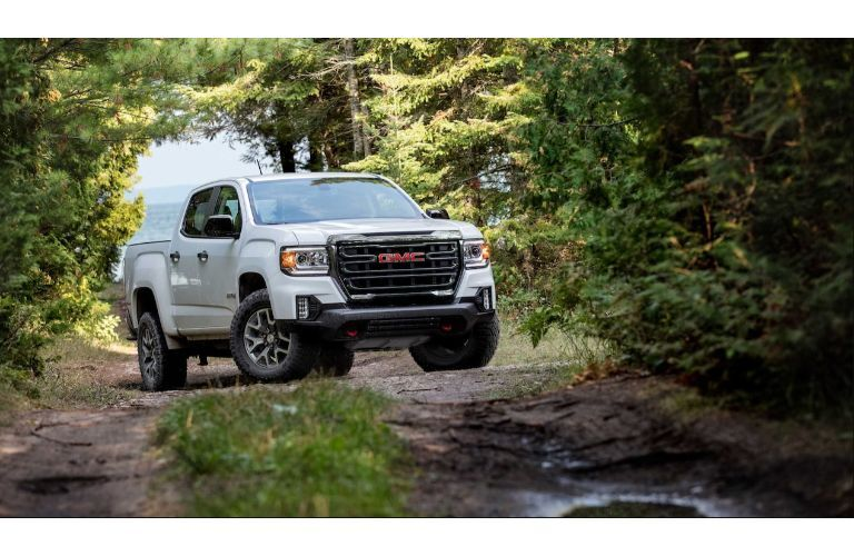 2021 GMC Canyon AT4 exterior shot with white paint color driving down a dirt road in a forest