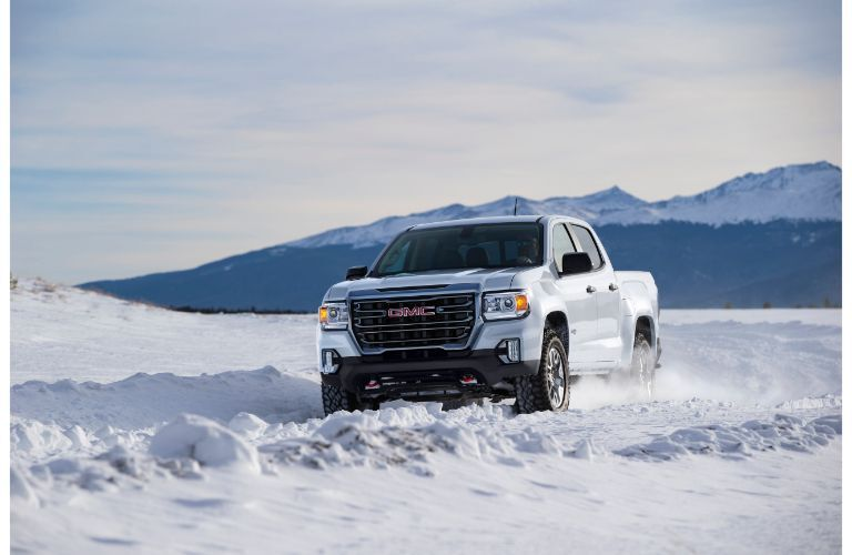 2021 GMC Canyon AT4 exterior shot with white paint color driving through a field of snow