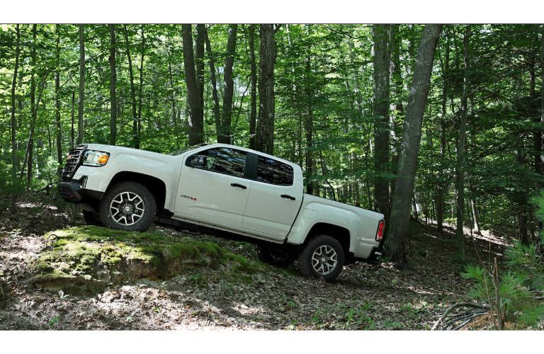 2021 GMC Canyon AT4 exterior side shot with white paint color climbing up rough terrain in a dense green forest