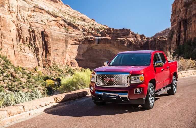 2021 GMC Canyon Denali exterior shot with red paint color driving on a desert mountain road