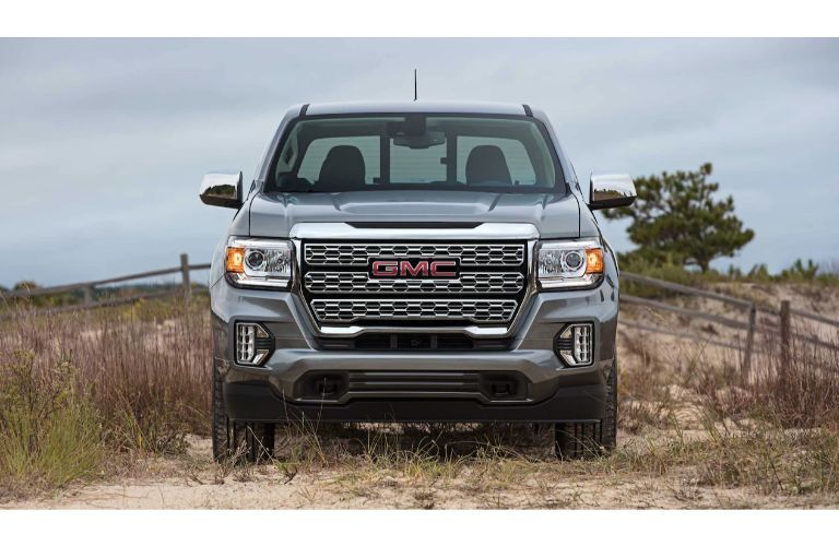 2021 GMC Canyon exterior front shot showcasing headlights and grille while parked in a dry field