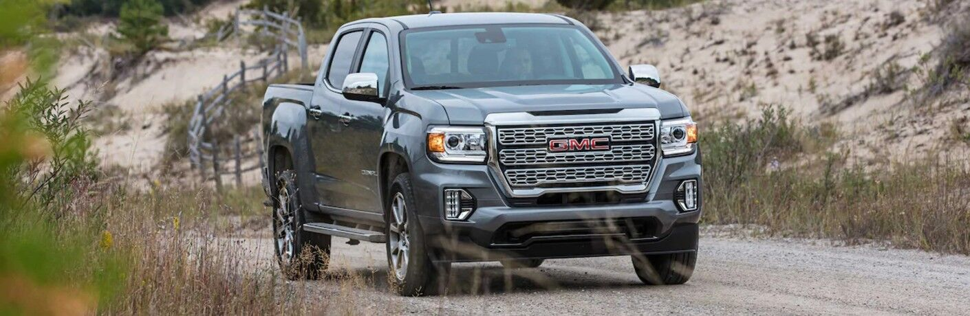 2021 GMC Canyon exterior shot with dark gray metallic paint color driving down a country road