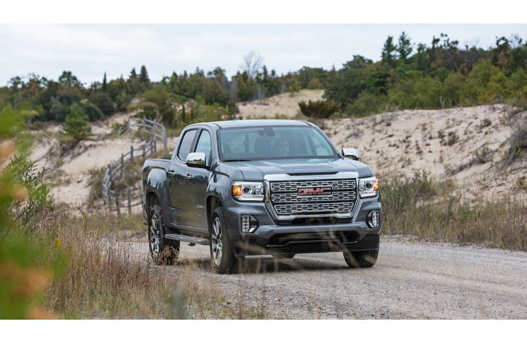2021 GMC Canyon exterior shot with gray metallic paint color driving down a country road