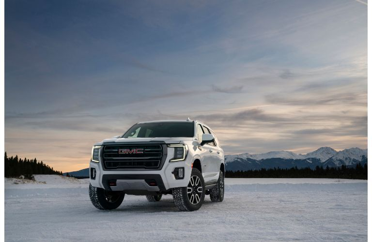2021 GMC Yukon AT4 exterior shot with white paint color with snowy mountains in the background and a setting sun