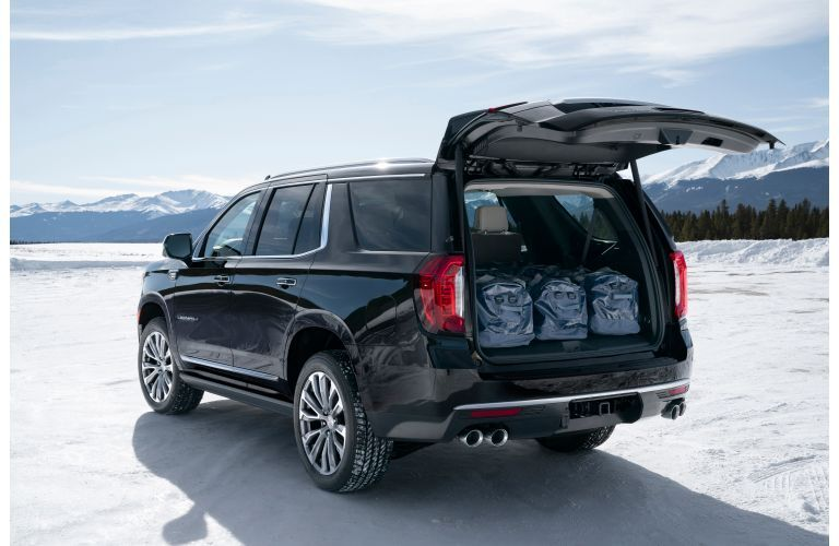 2021 GMC Yukon Denali exterior rear shot with trunk open and packed with luggage and bags