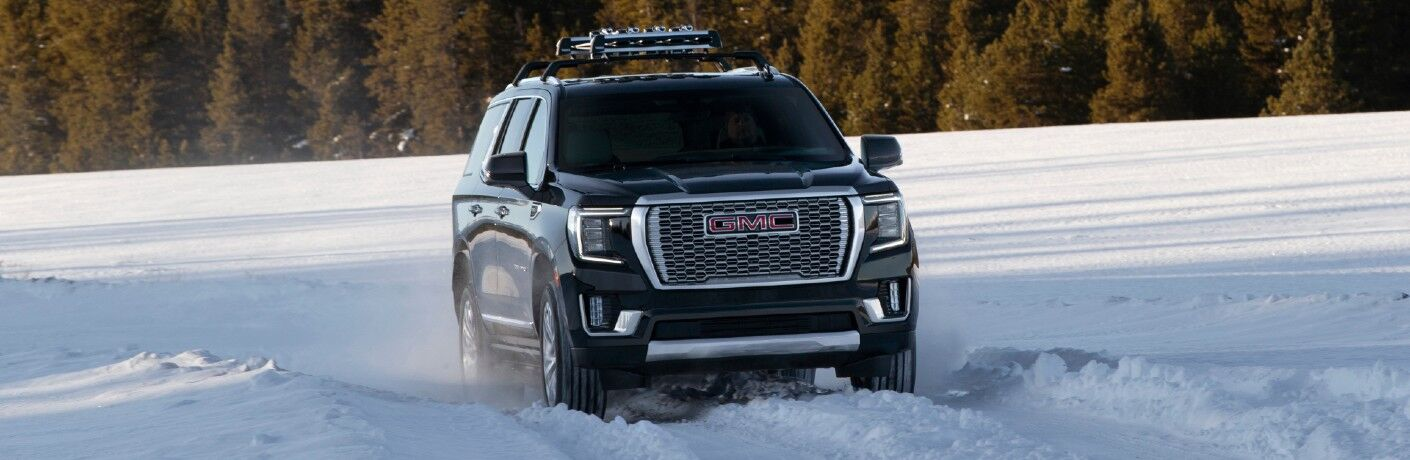 2021 GMC Yukon Denali exterior shot with roof rack and light bar attached while driving through the snow with a forest in the background