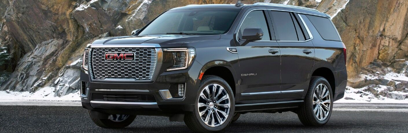 2021 GMC Yukon Denali exterior side shot against a snowy mountain cliff background