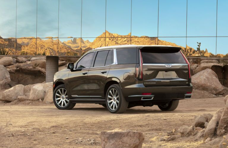 A photo of the 2021 Escalade ESV parked by a glass building.