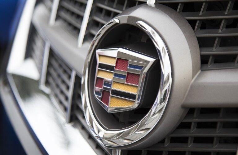 exterior closeup of Cadillac logo badging on grille