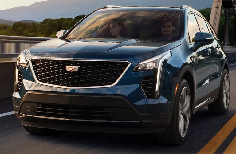 2019 Cadillac XT4 exterior shot with dark blue paint color driving over a bridge