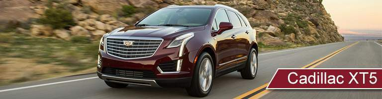 Red 2018 Cadillac XT5 driving down the road