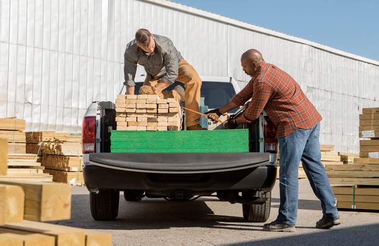 Two men loading slabs of wood into bed of 2018 Ram 1500