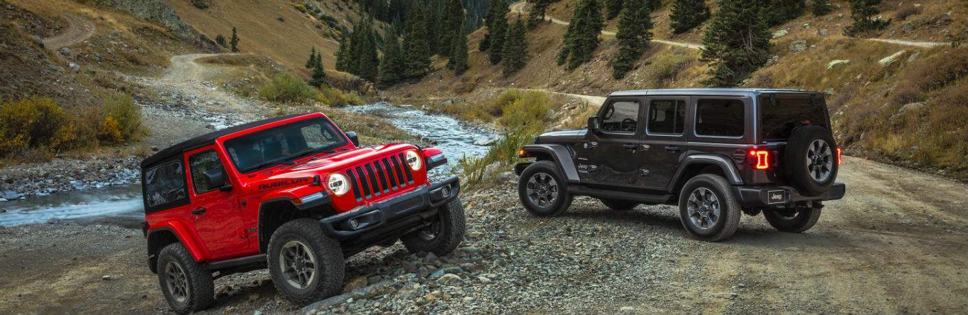 Two Jeep Wranglers parked on a hill near water