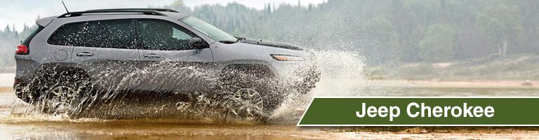 Gray Jeep Cherokee driving through muddy puddle