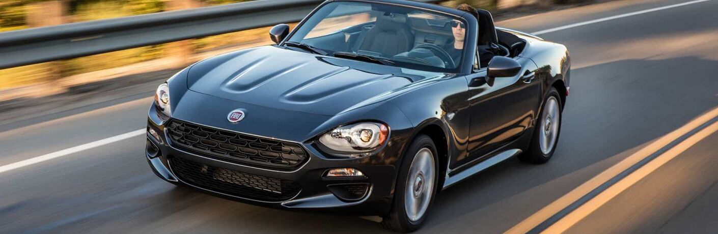 black fiat 124 spider driving on a road