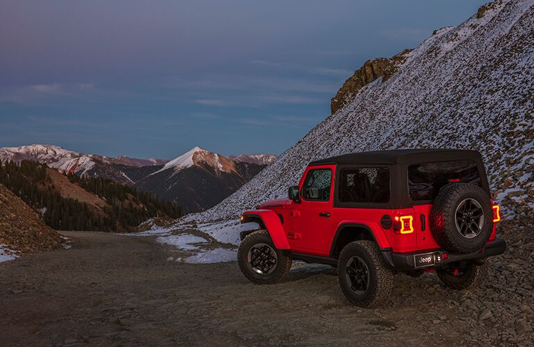rear quarter view of a 2018 Jeep Wrangler at the base of a mountain