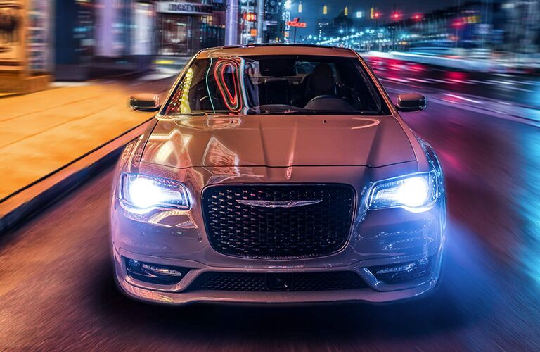 exterior front view of 2019 Chrysler 300 driving through city at night
